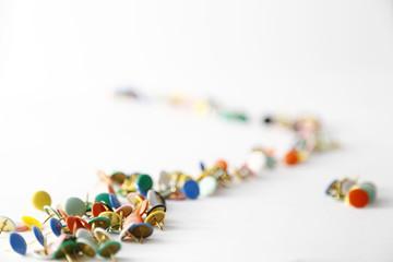 Puntine colorate in fila su sfondo bianco