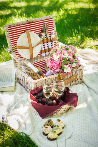 Two glasses of white wine with picnic basket.  - 54379531