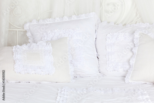 Beautiful and soft white laced pillows lie on white double bed.