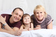 Happy father, little daughter and mother lie on white double bed