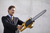 Angry businessman wielding a chainsaw.