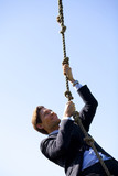 Businessman climbing rope
