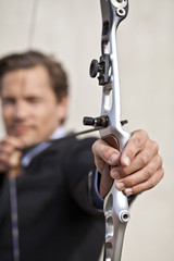 Determined businessman aiming bow
