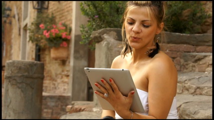 Fashion woman has video conference by tablet in Tuscany