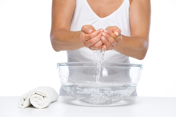 Closeup on woman washing hands in glass bowl with water