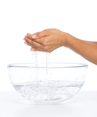 Closeup on young woman washing hands in glass bowl with water