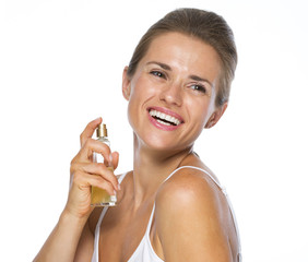 Happy young woman applying perfume