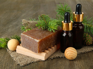 Hand-made soap and bottles of fir tree oil on wooden background