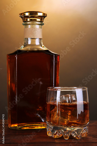 Brandy with ice on wooden table on brown background