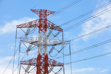 High voltage powerline and pylon against bright blue sky