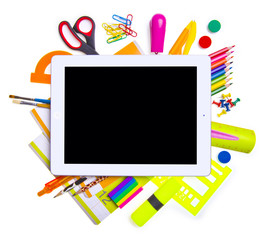 Tablet computer with school and office supplies.