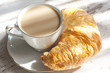Croissant and cup of coffee in the morning breakfast closeup