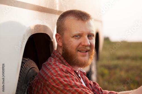 Cheerful man sitting near the car