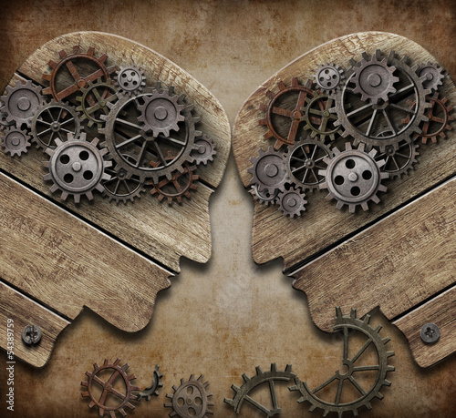 two wooden heads with gears coming into collision concept