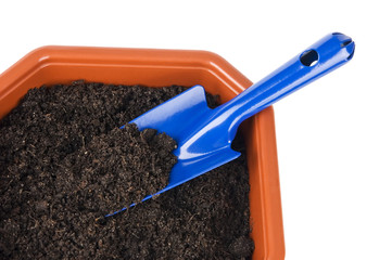 Flower pot with soil and shovel close up isolated on white