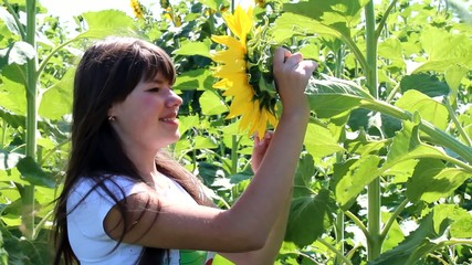young girl playing with blooming sunflower