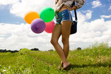 Girl with colored balloons in the field