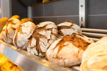 Shelf with loafs of bread in baker's shop