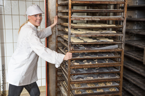 Baker filling oven in a bakery or bakehouse