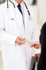 male doctor receiving money from a patient