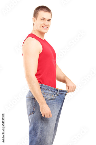 Satisfied weight less man in an old pair of jeans looking at cam