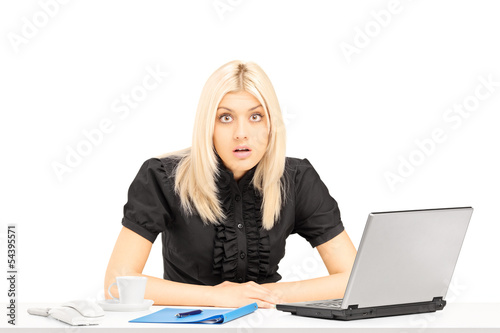 Surpised blond woman sitting on a table in her office
