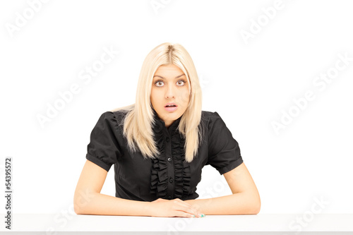 Surpised young woman sitting on a table