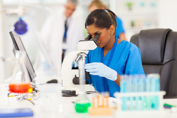 young medical researcher looking through microscope