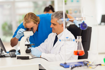 medical researchers working with microscope