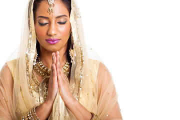 indian woman praying with eyes closed