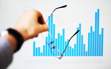 Image of hand pointing on a graph data