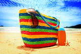 Colorful straw bag, sunglasses, sun lotion and starfish on beach