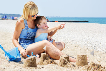 A happy  mother and  son having fun in the sand together