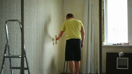 Young man spreading glue over wall before attaching wallpapers.