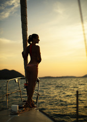 Young sexy woman in bikini enjoying the sunset on yacht