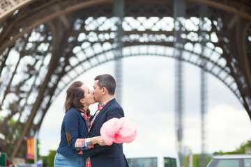 Couple with cotton candy under the Eiffel tower