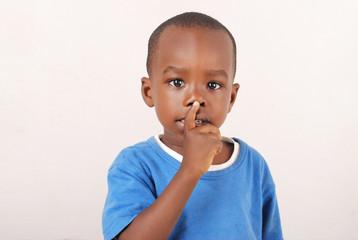 Un enfant avec le doigt sur la bouche