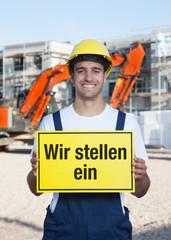 Bauarbeiter mit Schild WIR STELLEN EIN