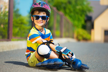 Cute little boy in sunglasses with rollers