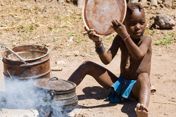 Native Himba boy cooking lunch