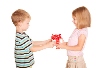 Little boy giving a little girl a gift.
