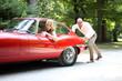 Mann schiebt Frau mit Oldtimer