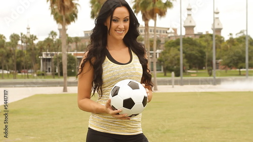 Sexy happy woman with football at park