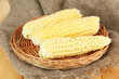 Fresh corn on wicker mat, on sackcloth background