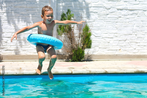 Preschool boy are jumping to the swimming pool