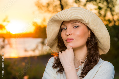 Young and beautiful woman wearing a hat in sunset light