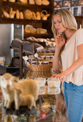 Happy young woman selecting bread from display cabinet of bakery