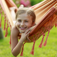Rest in the garden - lovely girl in colorful hammock