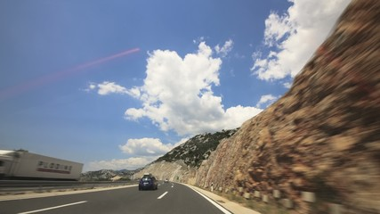 Driving a car over a mountain highway through tunnels