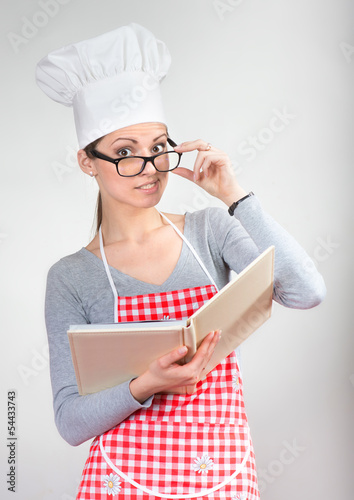 Funny portrait of a woman with cookbook looking over glasses